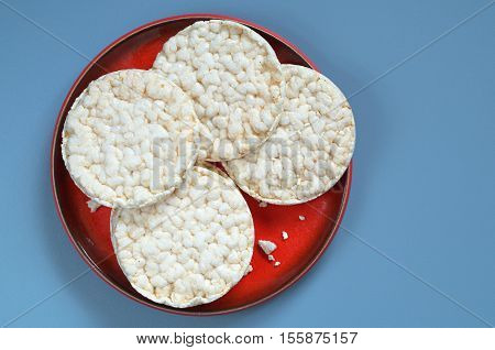 Round rice cakes in red plate on blue background top view