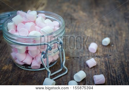 Pink and white mini marshmallows in a jar on an old rustic wooden table with space for text. Mini white and pink puffy marshmallows. Marshmallow concept. Copy space. Selective focus.