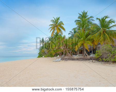 Tropical island in Indian Ocean. White sand beach. Palm trees and tropical vegetation on the coast. Blue sky covered with clouds.