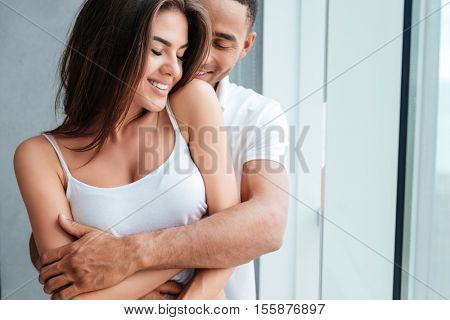 Pretty couple near window. interracial couple. so happy