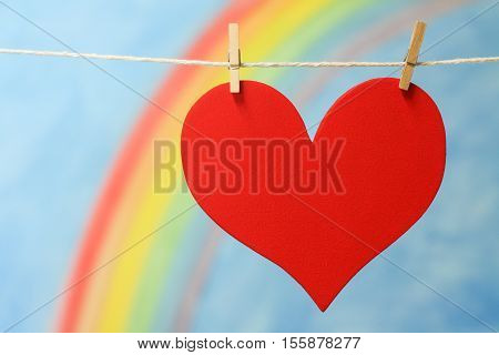 A red heart symbol representing love, lust and hope, with a blue sky and colorful rainbow.
