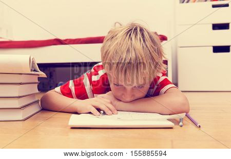little boy hates and tired of doing homework