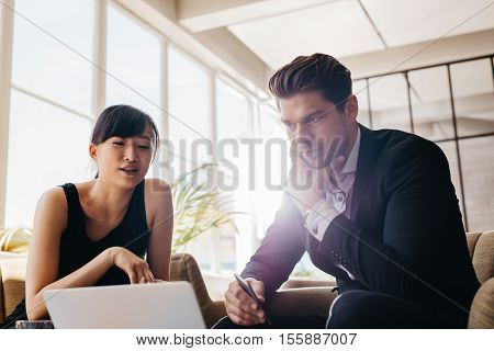Young Businesspeople Working On Laptop In Office