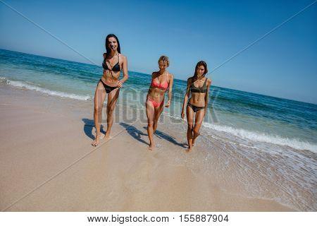 Full length shot of sexy young female bikini models walking out of sea water. Women catwalk on the beach.