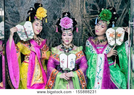 three attractive asian women wearing japanese kimono holding traditional fans