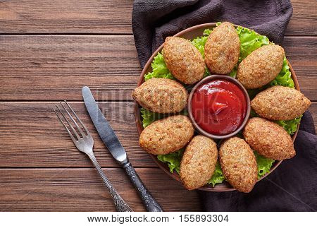 Kibbeh middle eastern beef, lamb, goat or camel meat stuffed bulgur kofta spicy meatball fried croquettes dinner on green salad food on rustic wooden table background