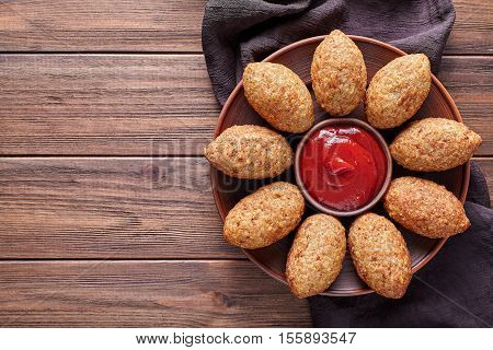 Kibbeh traditional homemade arabic beef, lamb, goat or camel meat stuffed bulgur kofta spicy meatball fried croquettes dinner food on rustic wooden table background