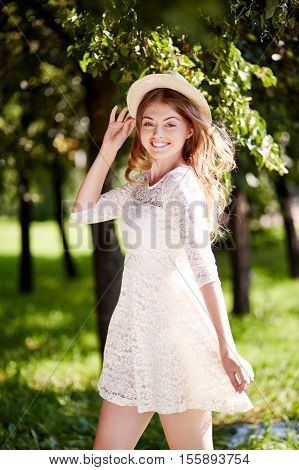 Happy teenage girl in lace dress and straw hat posing in the park