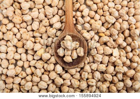 Raw Chick Peas Background And A Wooden Spoon