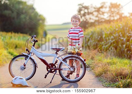 Happy school kid boy having fun with riding of bicycle. Active child making sports with bike in nature. Safety, sports, leisure with kids concept.