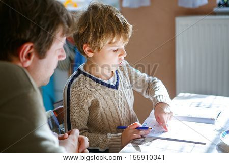 Cute little preschool kid boy at home making homework with dad. Little child writing with colorful pencils, father helping him, indoors. Elementary school and education.