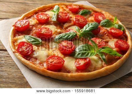 Fresh tasty pizza Margarita on baking paper, closeup