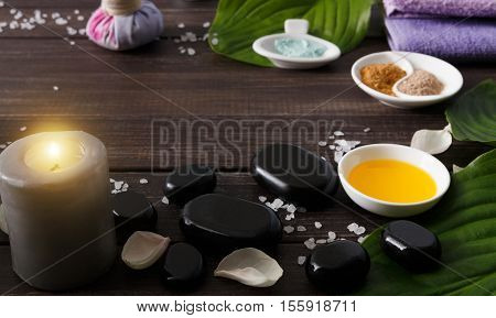 Spa treatment and aromatherapy concept background. Zen stones, aroma salt, spices, burning candle, oil and soap, candle and other details of wellness body care and alternative indian medicine.