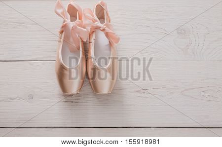 Pastel pink ballet shoes background. New pointe shoes with satin ribbon lay on white rustic shubby chic wood, top view with copy space