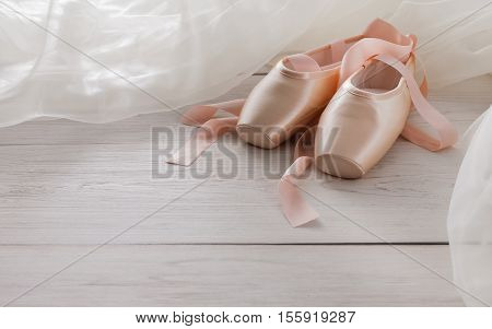 Pastel pink ballet shoes background. New pointe shoes with satin ribbon and chiffon tutu lay on white rustic shubby chic wood, copy space