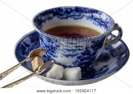 Antique blue and white china cup and saucer of black English breakfast tea with silver tongs for white and brown sugar cubes. Isolated on white background with copy space.