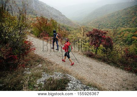 male and female hikers with walking poles travelling on a mountain trail in autumn rain