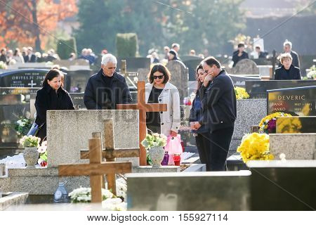 People Praying At Grave