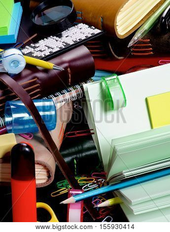 Background of Stationery Items with Notepads Pens Pencils Paper Clips Tape Dispenser Sharpener Stickers Loop and Markers closeup