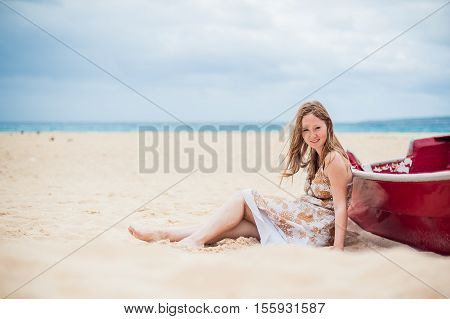 A Young Girl Sits On The Beach Leaning Against A Boat