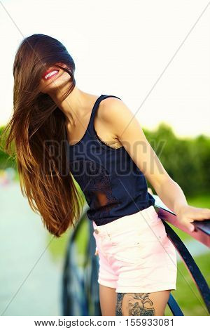Funny stylish sexy smiling beautiful sunbathed young woman model in summer bright hipster cloth in the park with blowing hair in the wind