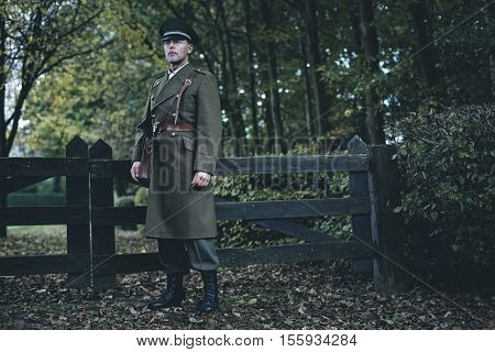Retro 1940S Military Officer Standing At Wooden Fence In Autumn Forest.