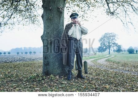 Retro 1940S Military Officer With Coat Over Shoulder Smoking Cigarette Under Tree.