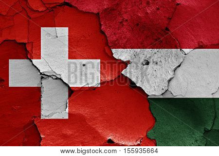 flags of Switzerland and Hungary painted on cracked wall