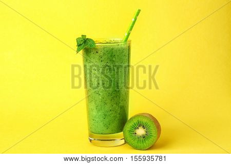 Glass of delicious kiwi milk shake on yellow background