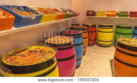 A stock of multi-colored candies in many funny shapes placed in colorful wooden barrels and boxes.