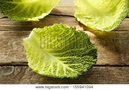 Savoy cabbage leaves on wooden table