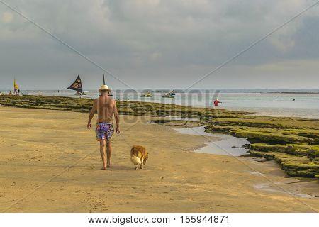 PORTO GALINHAS, BRAZIL, JANUARY - 2016 - Old man walking with his dog at tropical beach in Porto Galinhas Pernambuco Brazil