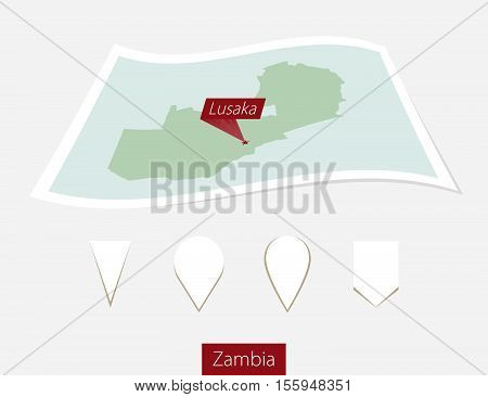 Curved Paper Map Of Zambia With Capital Lusaka On Gray Background. Four Different Map Pin Set.