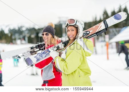 Beautiful young woman friends enjoying in winter vacations. They standing with skis and looking at camera with smile.
