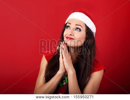 Praying Happy Woman In Santa Claus Christmas Costume Looking Up And Making A Wish On Red Background