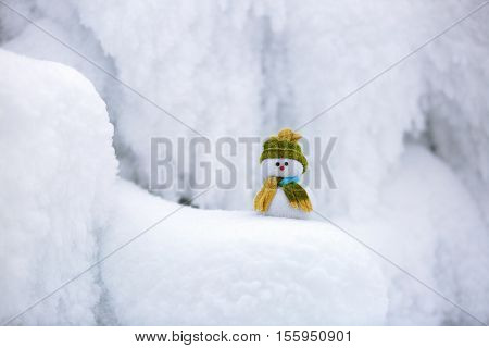 the snowman in hat and scarf is standing on fascinating fluffy snow near the hill and around there are frozen textured patterns.