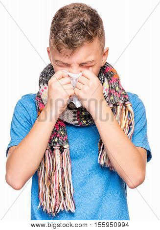 Healthcare and medicine concept - ill teen boy with flu blowing nose.  Child wearing blue t-shirt and scarf.