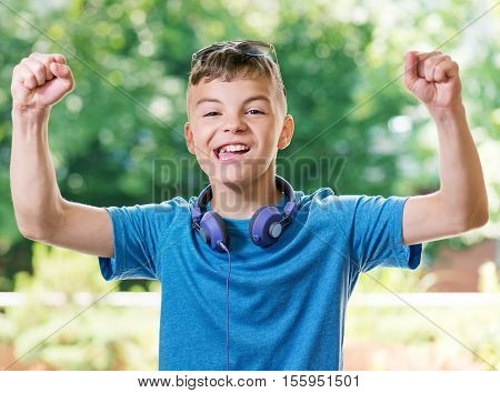 Victory screaming teen boy 12-14 year old. Funny winner boy with headphones and sunglasses posing outdoors. Portrait of a happy handsome teenager shouting with his hands up in summer park.