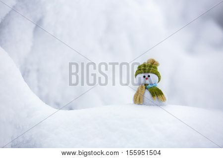 Nice dreaming snowman in green hat is standing on interesting textured snow near to the hill on cold winter day.