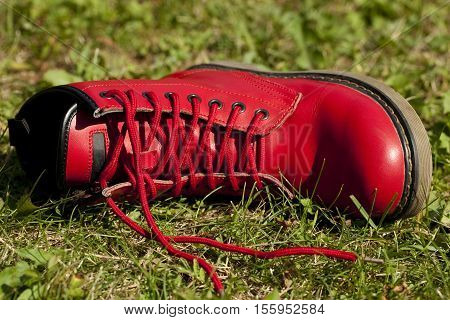 woman red leather shoe lies on grass