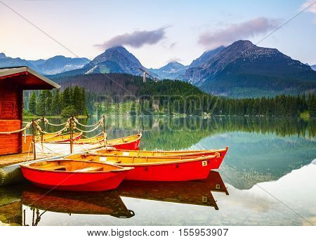 Red boats moored at wooden house on a lake with a clear water against the background of high mountains.Strbske Pleso lake Slovakia Tatra mountains