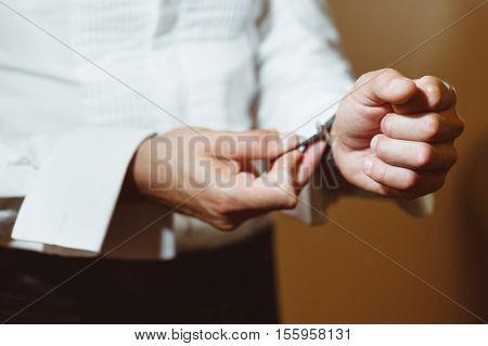 Pre-wedding preparation. Bridegroom fixing his cuff. White shirt. Closeup