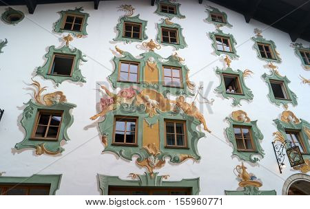 St. Johann, Austria - October 13, 2016: Painted wall of a house in the Tyrol. The windows are decorated with an elegant pattern. In one of the windows looking out girl.
