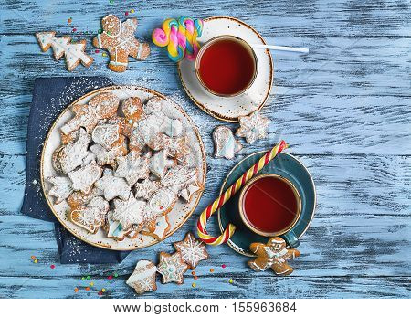 Christmas sweets baking gingerbread cookies on the plate. Decorated for Christmas gingerbread cookies christmas bumps. Christmas cookies gingerbread on blue table tea drink. New Year food. Top view