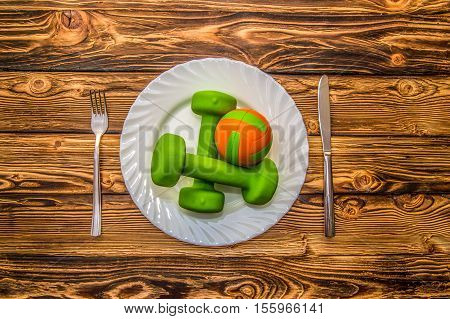 Dumbbells ball and expander on a plate as a breakfast concept of healthy lifestyle on a wooden table