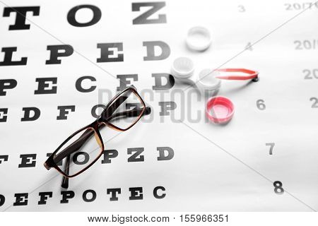 Glasses, lenses container and pincer on eye test chart, close up view. Healthy eyes concept