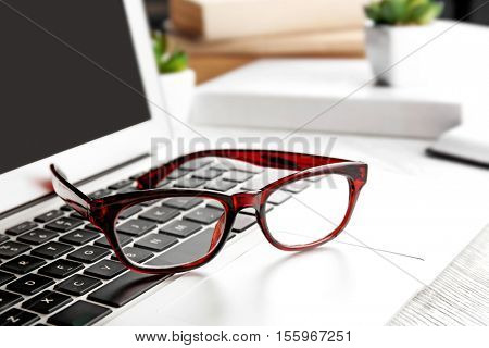 Glasses lying on laptop, close up view. Healthy eyes concept