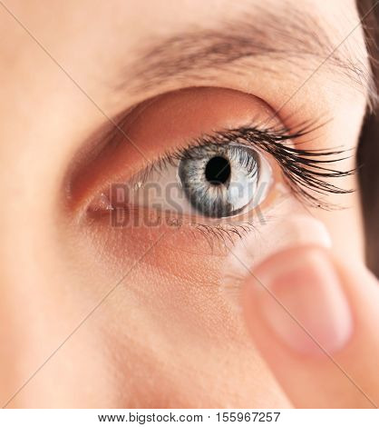 Close up view of young woman putting contact lens in her eye