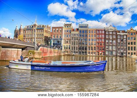 AMSTERDAM, NETHERLANDS - MAY 3, 2016: City view of canals dutch houses and tour boat, Amsterdam, Netherlands. Amsterdam is known as Venice of the North it has 1200 bridges and 165 canals. Best way to experience them is one of the boat tours.