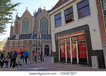 AMSTERDAM, NETHERLANDS - MAY 5, 2016: View of The Old Church (Oude Kerk) in Red-light district in Amsterdam, Netherlands.